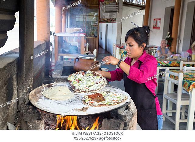 Santiago Matatlán, Oaxaca, Mexico - A worker makes tlayudas on a comal in a Oaxaca restaurant