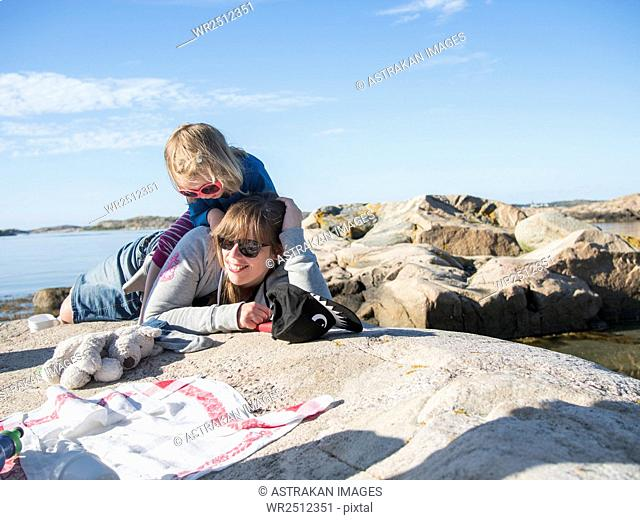 Mother and daughter enjoying summer vacation on lakeshore