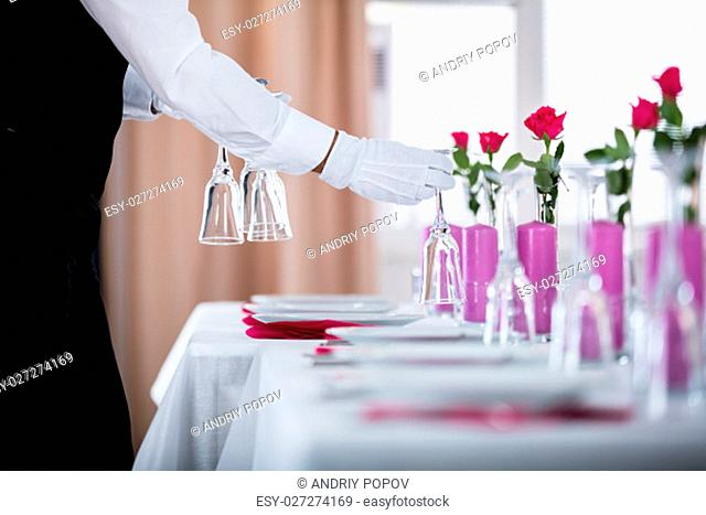 Close-up Of Waiter Setting Wedding Table At Restaurant