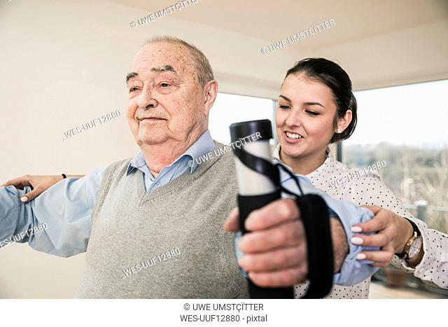 Young woman supporting senior man doing an arm exercise