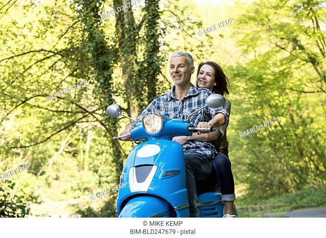 Caucasian couple riding blue motor scooter