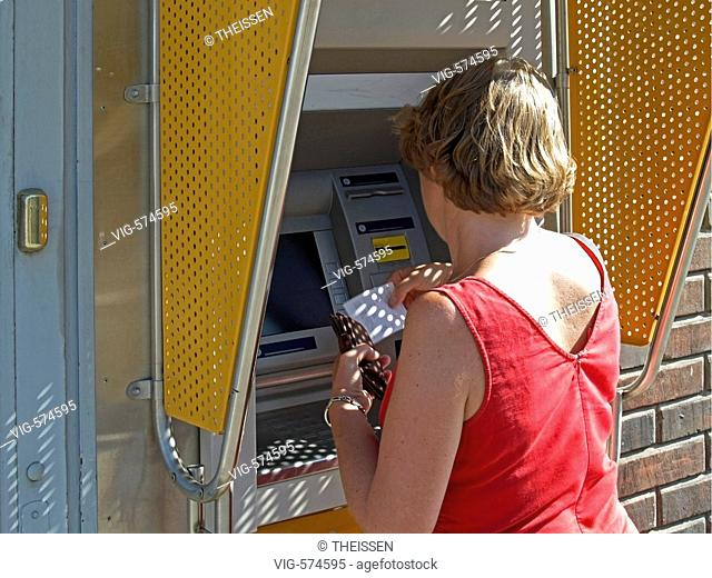 woman getting money from an automated teller machine ATM cash point bancomat. - 07/08/2006