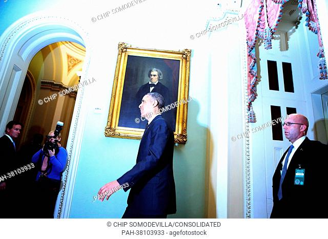 Illuminated by other photographers' flashes, United States President Barack Obama leaves after meeting with members of the Senate Democratic Caucus in the...