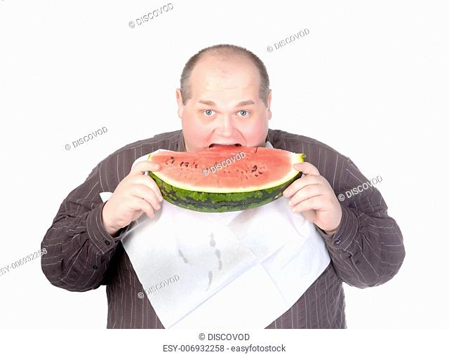 Obese man with a serviette bib around his neck standing eating a large slice of fresh juicy watermelon isolated on white