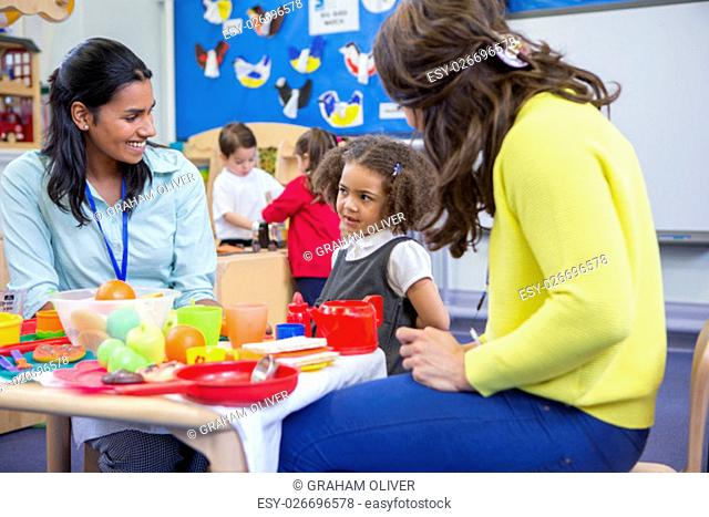 Teachers playing with plastic kitchen toys with their nursery students in the classroom