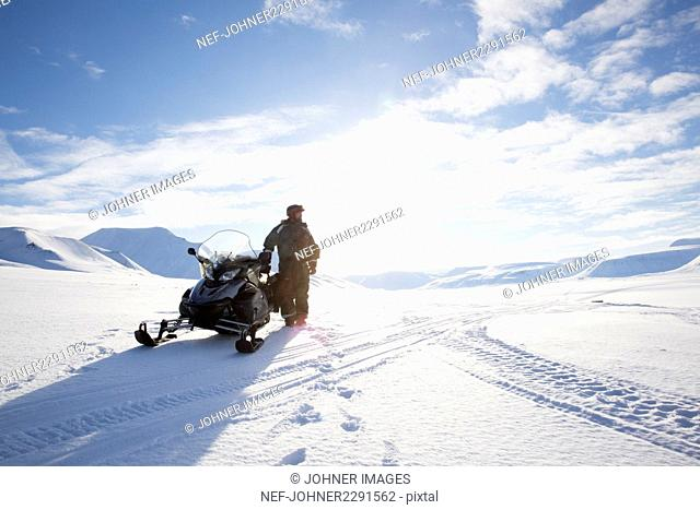 Man standing next to snowmobile in winter landscape