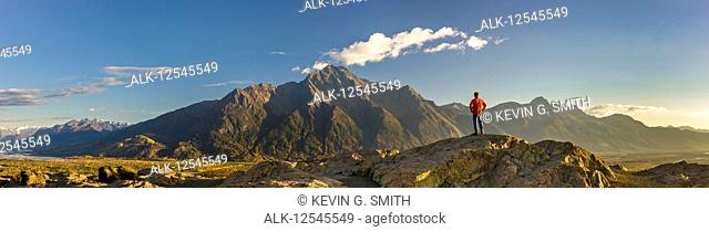 Panoramic view of a man standing atop the Butte, Pioneer Peak and the Knik River in the background at sunset, South-central Alaska; Palmer, Alaska