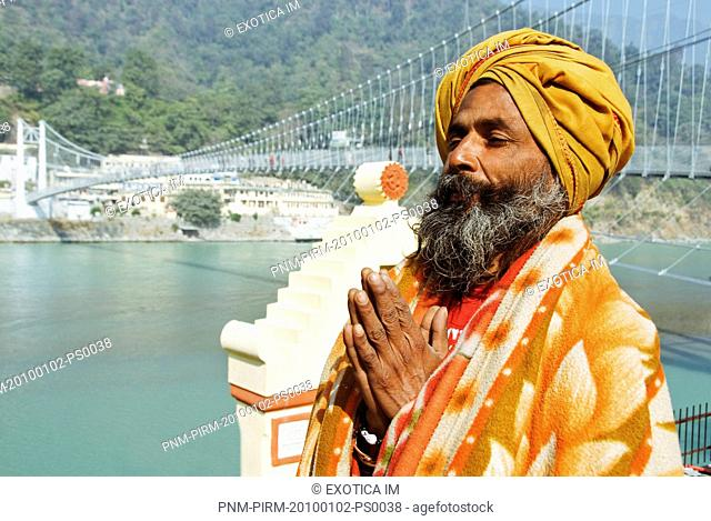 Close-up of a sadhu praying with a suspension bridge in the background, Lakshman Jhula, Ganges River, Rishikesh, Dehradun District, Uttarakhand, India