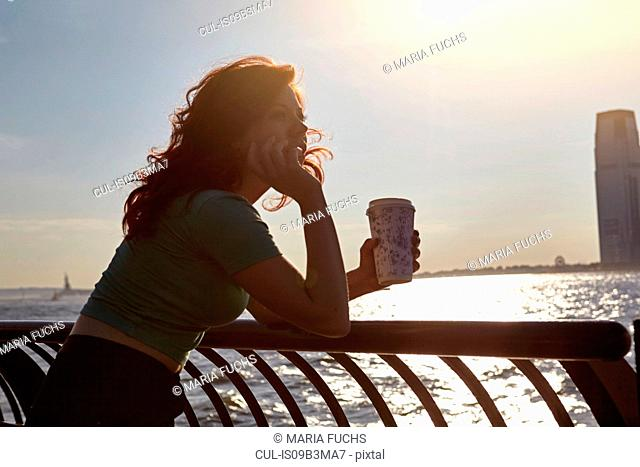 Young female tourist leaning against waterfront railing with coffee, Manhattan, New York, USA