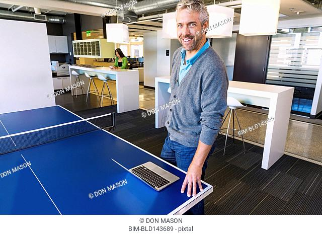 Businessman using laptop at table tennis table in office