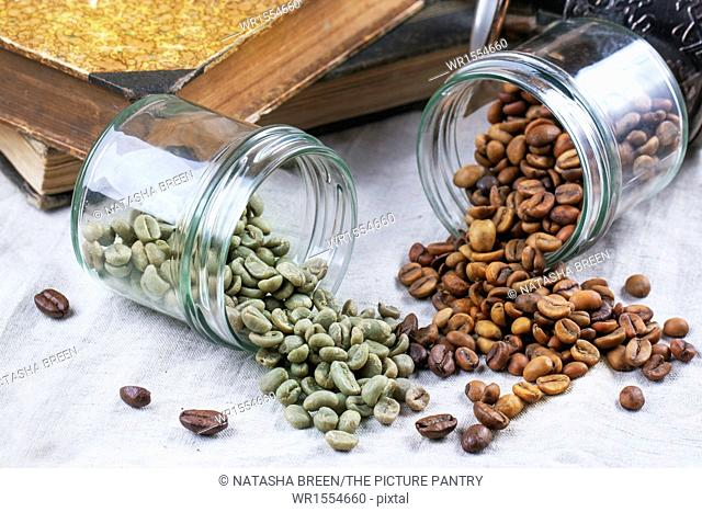 Glass jars with green and brown decaf unroasted coffee beans on table with vintage books