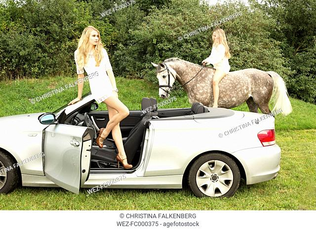 Young woman standing in a cabriolet while teenage girl riding on a horse in the background