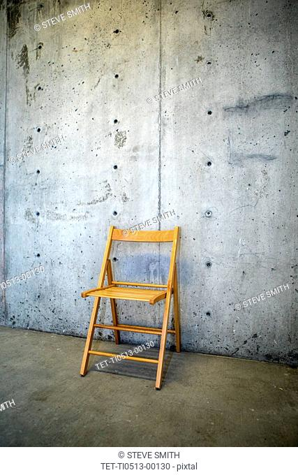Folding chair by concrete wall