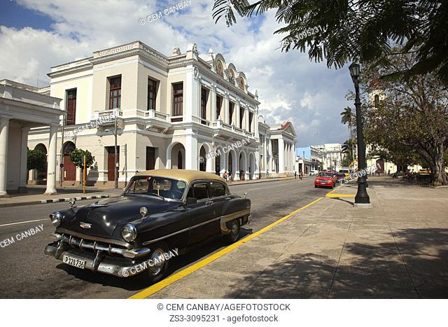 Old American car in front of the Tomas Terry Theatre-Teatro Tomas Terry at Jose Marti Park in Plaza De Armas Square, Cienfuegos, Cuba, West Indies