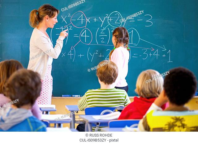 Primary school teacher explaining equation on classroom blackboard