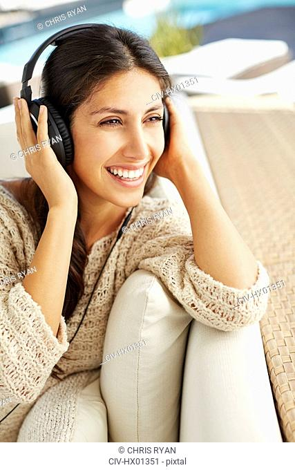 Smiling woman listening to music with headphones on sofa