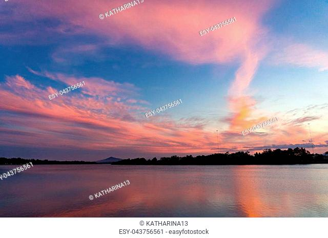 Breathtaking pink and blue sunset sky over river with colorful clouds reflected in water. Nature landscape background