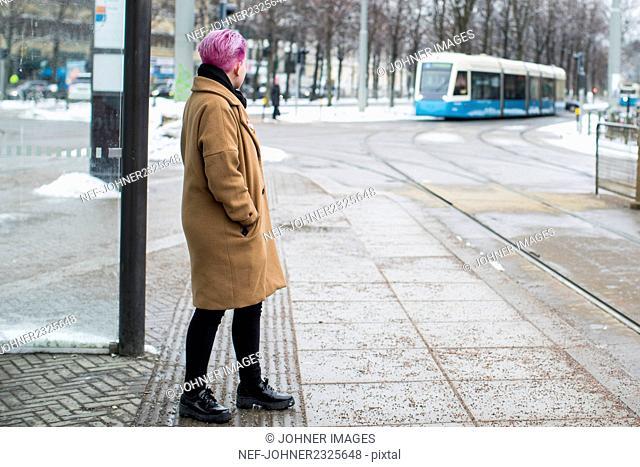 Young woman at bus stop