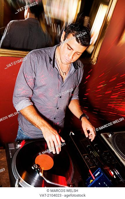 Disc jockey plays recorded music from a vinyl record, gold coast queensland australia