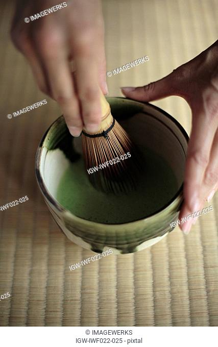 View of a person grinding with a pestle