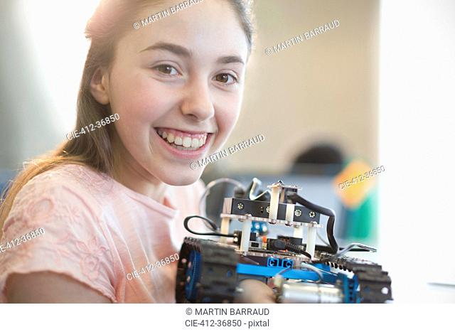 Portrait smiling, confident girl student holding robot