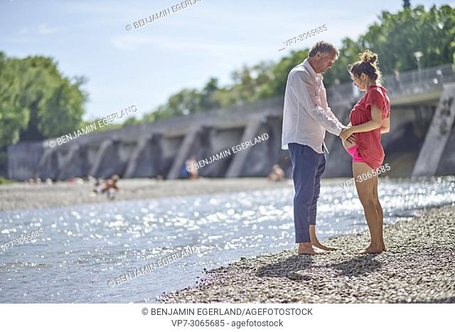 Couple, pregnancy, exercising, age difference, togetherness. At river Isar, Munich, Germany