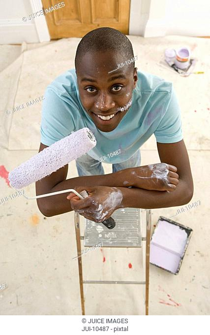 Young man on ladder with paint roller, elevated view, smiling, portrait