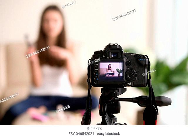 Close up photo of digital camera on tripod with young woman using cosmetics image on LCD back screen and blurred scene on background
