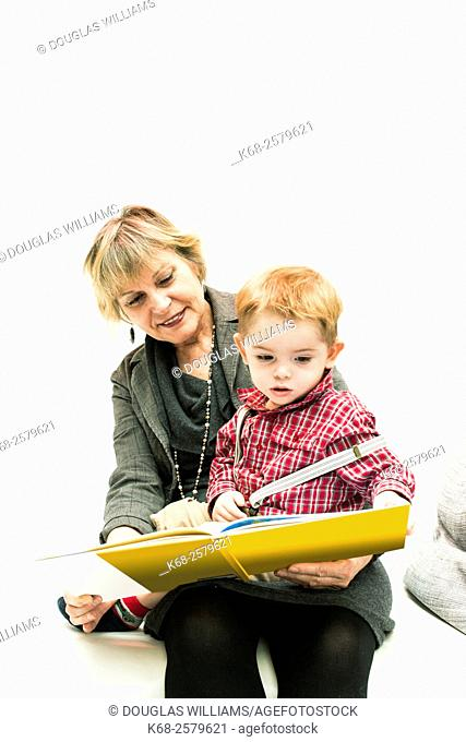 Studio shot of grandmother and grandson reading book