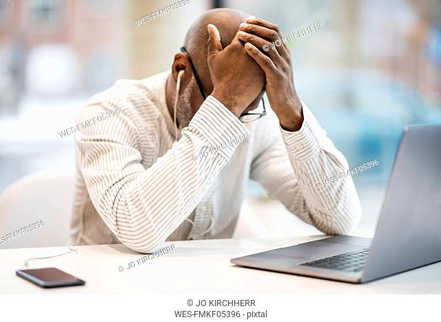 Mature businessman with earphones, smartphoen and laptop sitting with hands on head at desk