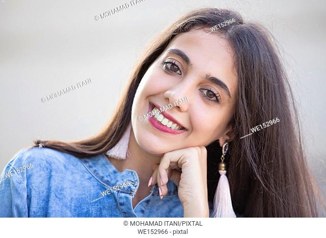 Close up portrait of a beautiful young Lebanese woman hand touching face smiling