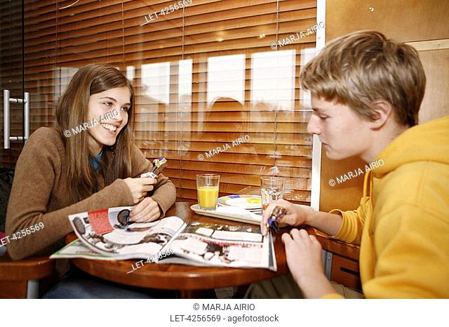 A girl sits with a boy in a cafe