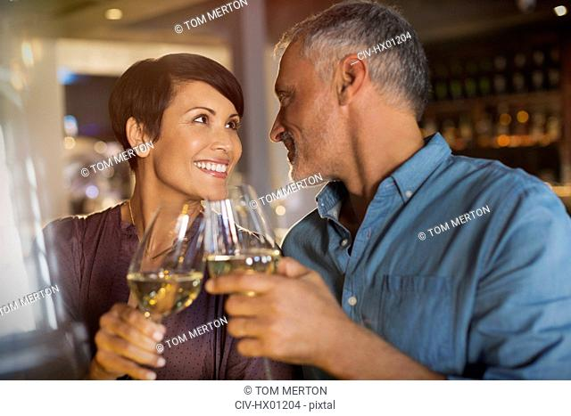 Couple toasting white wine glasses in restaurant
