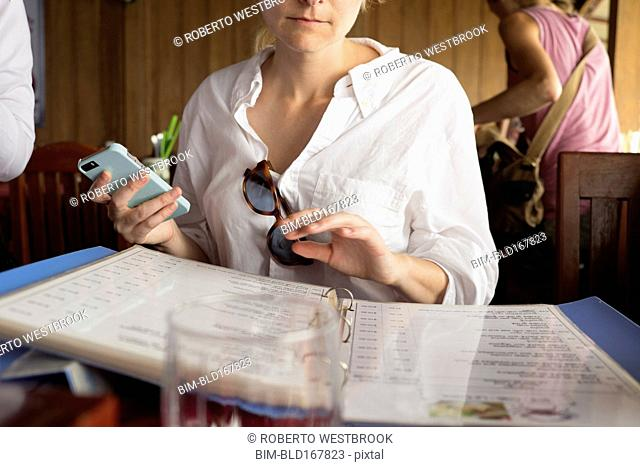 Caucasian woman reading menu in restaurant
