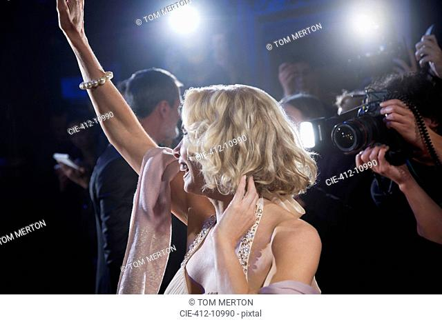 Female celebrity waving to paparazzi at red carpet event