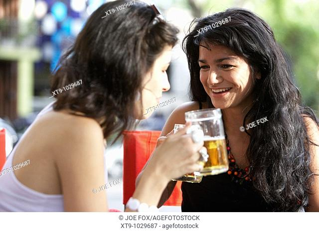 mid twenties hispanic women sharing a drink and enjoying a laugh at outdoor street cafe table