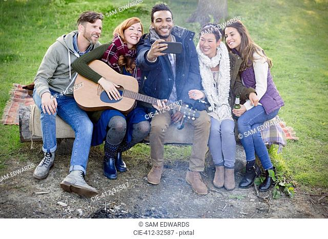 Friends with guitar taking selfie with camera phone at campsite