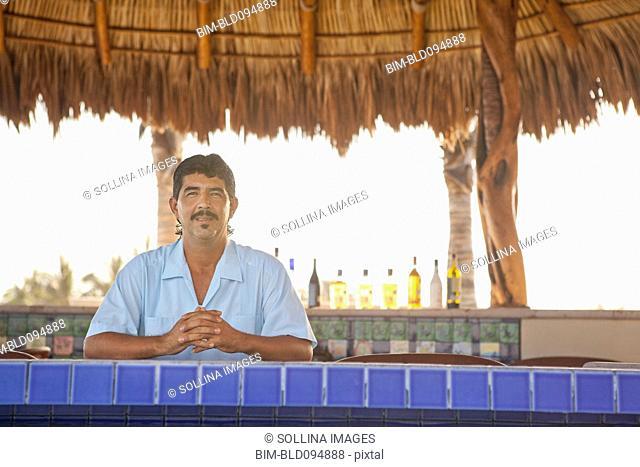 Hispanic bartender standing behind bar