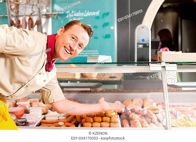 Working in a butchers shop - a butcher is showing the variety of sausages