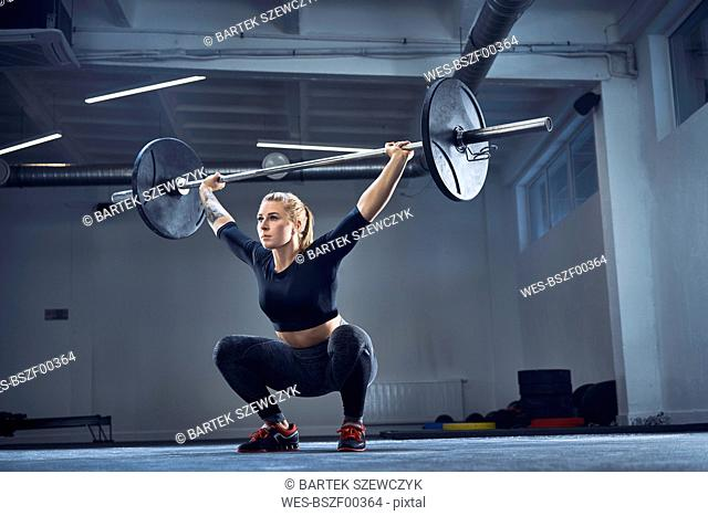Woman doing overhead squat exercise at gym