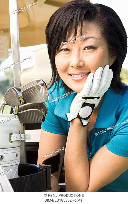 Korean woman smiling with golf clubs