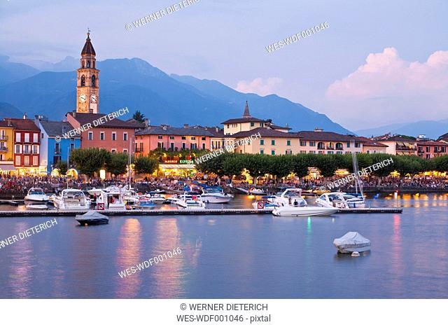 Switzerland, Ticino, View of Ascona at dusk with boats in Lake Maggiore
