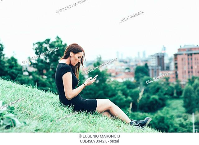 Young woman sitting on hillside reading smartphone texts above city