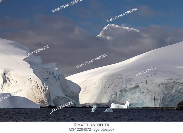 Glacier covered Melchior Islands, Peaks of Brabant Island in background, Antarctic Peninsula; Antarctica