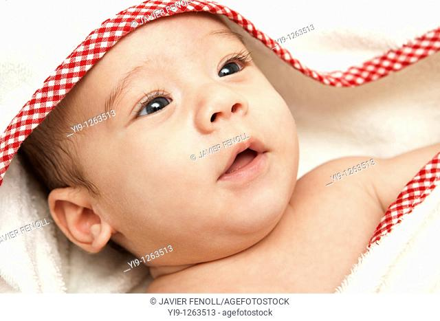A baby wrapped in a bath towel