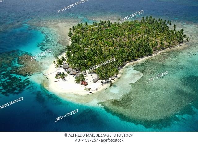 Aerial view of thatched houses and palm tree forest in island  San Blas archipelago, Caribbean, Panama, Central America