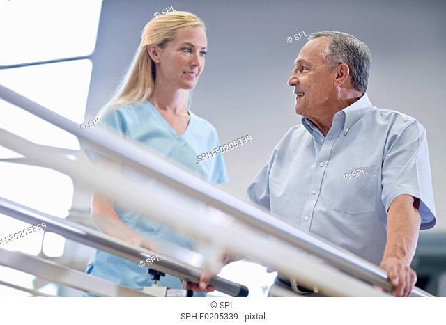 Nurse with senior man using parallel walking bars