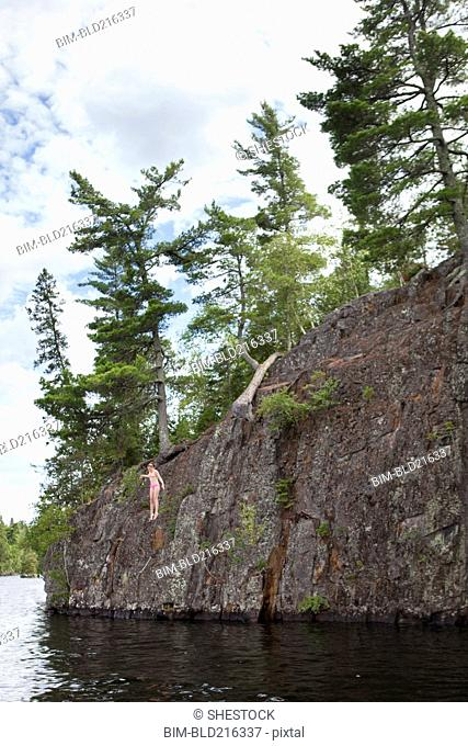 Caucasian girl jumping into lake from cliff