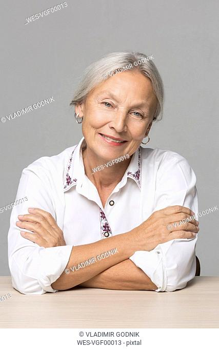 Portrait of senior woman with grey hair sitting at table