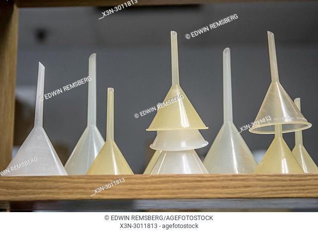 Stack of lab funnels sitting on wooden shelf, Tifton, Georgia. USA